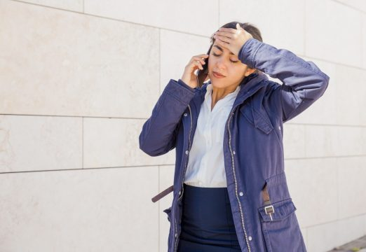 Tired office girl speaking on mobile phone outside. Frustrated young woman suffering from head ache and talking on cell. Bad news or fatigue concept